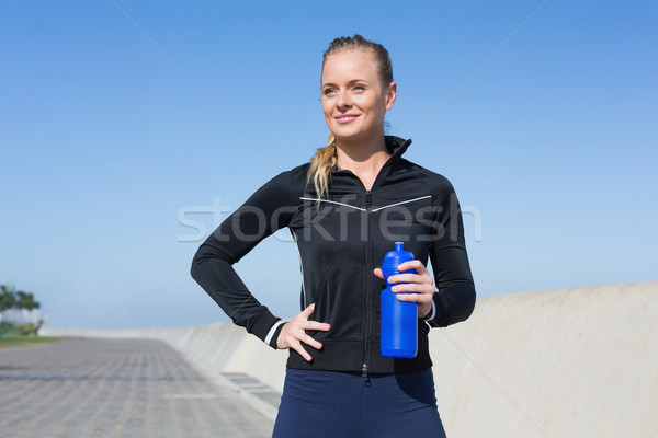 Fit blonde holding bottle on the pier Stock photo © wavebreak_media