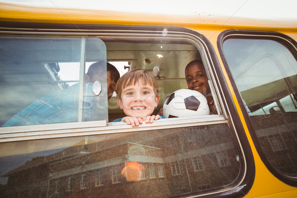 Cute pupils smiling at camera in the school bus Stock photo © wavebreak_media