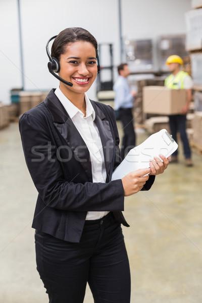 Warehouse manager wearing headset holding clipboard Stock photo © wavebreak_media