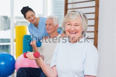 Instructor assisting senior woman in lifting dumbbells Stock photo © wavebreak_media