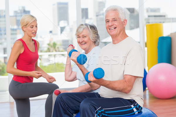happy senior couple lifting dumbbells while instructor guiding t Stock photo © wavebreak_media