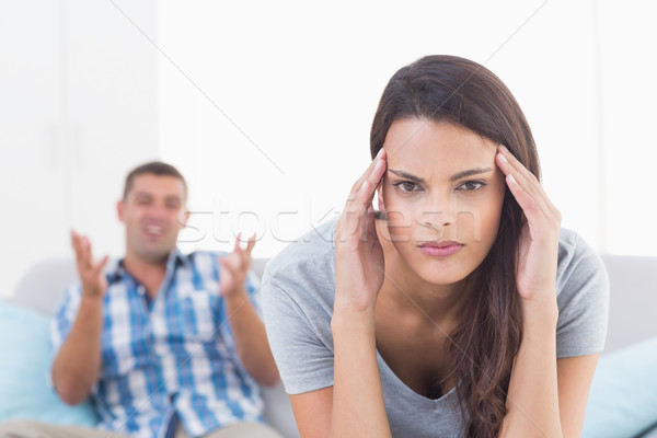 Woman suffering from headache while man arguing Stock photo © wavebreak_media