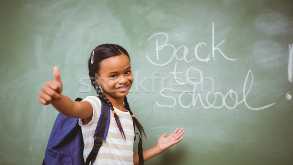 Stock photo: Little girl gesturing thumbs up in classroom