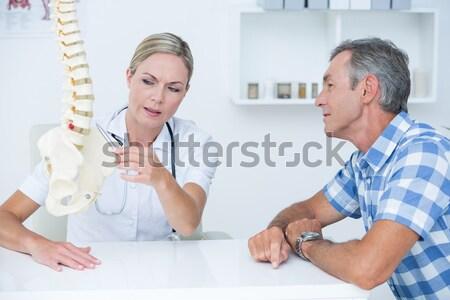 Doctor showing her patient a spine model Stock photo © wavebreak_media