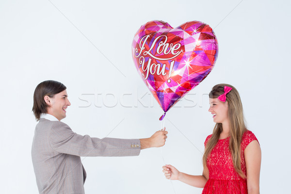 Geeky hipster offering red heart shape balloon to his girlfriend Stock photo © wavebreak_media