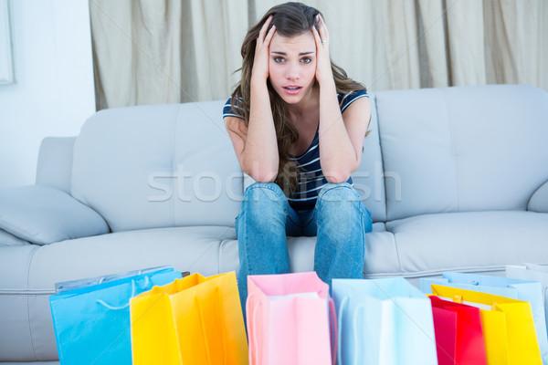 Regretful woman looking at many shopping bags  Stock photo © wavebreak_media