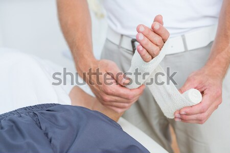 Physiotherapist examining her patients wrist Stock photo © wavebreak_media