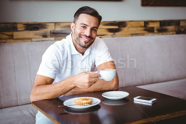 Young man drinking cup of coffee and pastry beside Stock photo © wavebreak_media