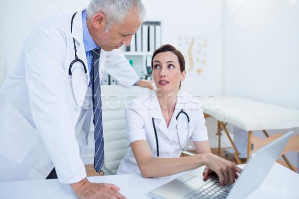 Geconcentreerde medische collega's bespreken werken laptop Stockfoto © wavebreak_media