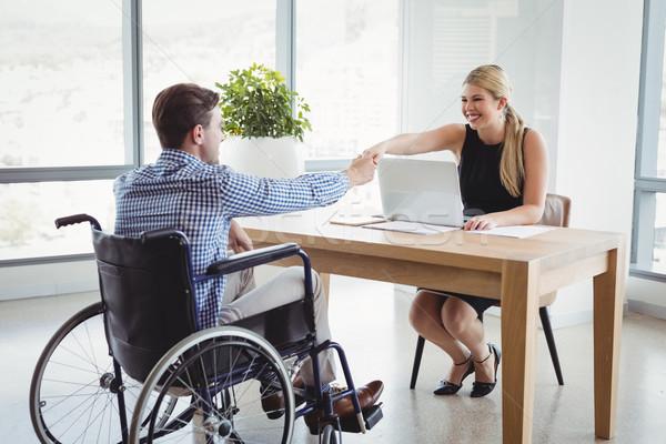 улыбаясь рукопожатием столе служба женщину Сток-фото © wavebreak_media
