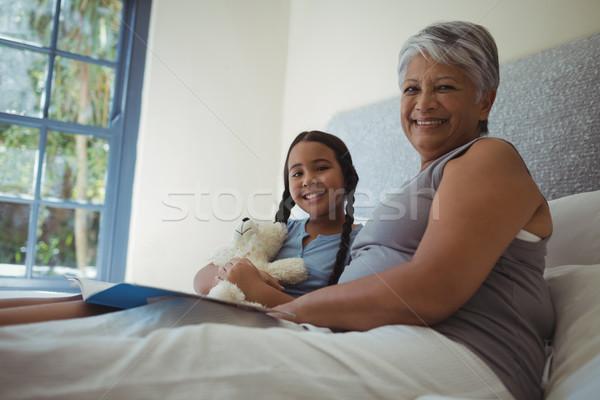 Grandmother and granddaughter holding photo album in bed room Stock photo © wavebreak_media