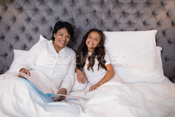 Cheerful grandmother and granddaughter resting on bed at home Stock photo © wavebreak_media
