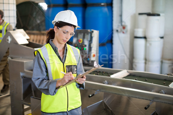 Female technician writing in clipboard Stock photo © wavebreak_media
