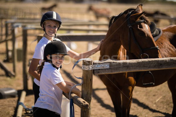 улыбаясь девочек Постоянный коричневый лошади ранчо Сток-фото © wavebreak_media