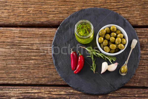 Green olives, fresh herbs with olive oil and red chilies on table Stock photo © wavebreak_media