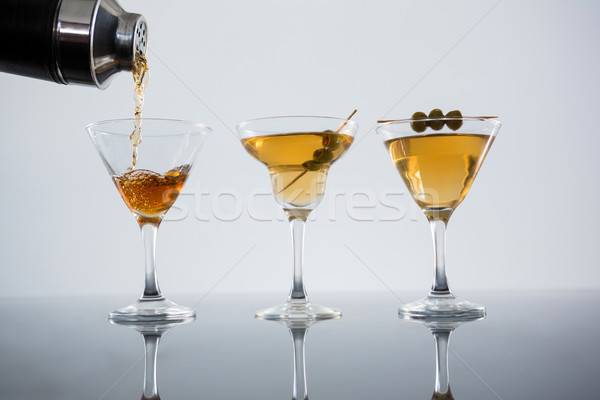 Cocktail poured in glass with olives on table Stock photo © wavebreak_media