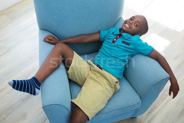 High angle portrait of boy lying on armchair at home Stock photo © wavebreak_media