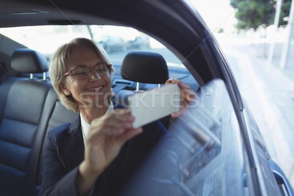 Businesswoman photographing in car Stock photo © wavebreak_media