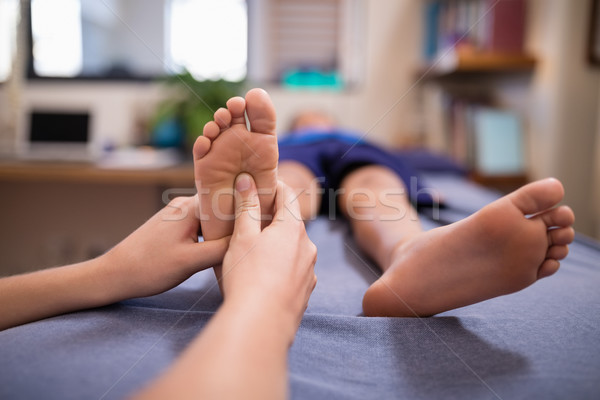 Female therapist massaging sole of foot while boy lying on bed Stock photo © wavebreak_media