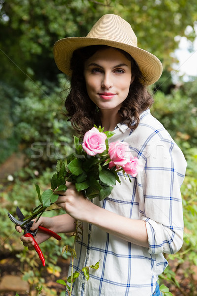 Woman trimming flowers with pruning shears in garden on a sunny day Stock photo © wavebreak_media