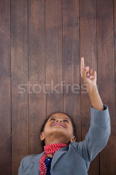 Souriant femme d'affaires pointant up permanent tête Photo stock © wavebreak_media