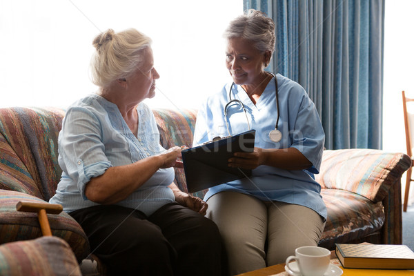 Senior woman discussing with doctor while reading book sofa Stock photo © wavebreak_media