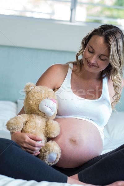 Pregnant woman sitting with a teddy bear Stock photo © wavebreak_media