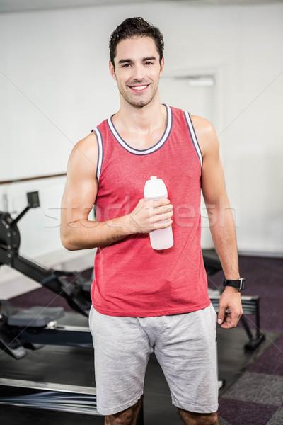 Uśmiechnięty człowiek stałego butelki wody Zdjęcia stock © wavebreak_media