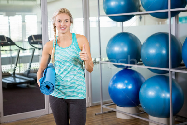 Fit blonde holding mat and showing thumb up Stock photo © wavebreak_media