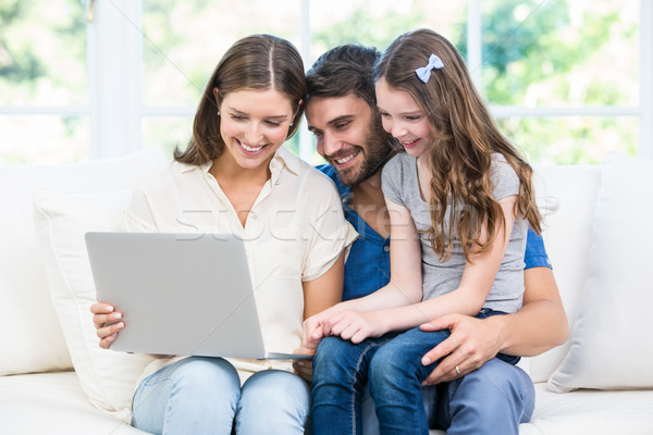 Family sitting on sofa and looking at laptop  Stock photo © wavebreak_media