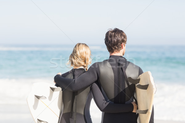 Rear view of couple in wetsuit with surfboard standing on the be Stock photo © wavebreak_media