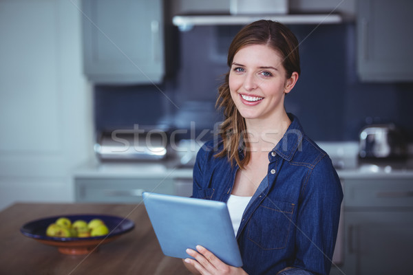Beautiful woman using digital tablet in kitchen Stock photo © wavebreak_media
