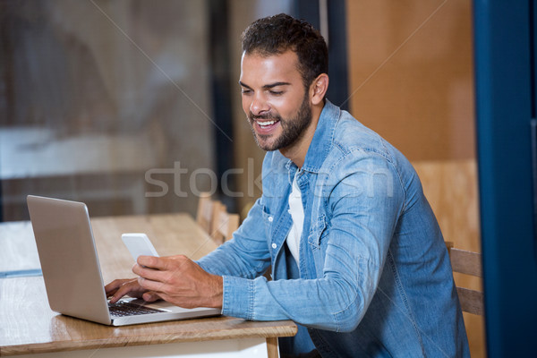 Man text messaging on phone while sitting on desk with laptop Stock photo © wavebreak_media