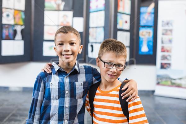 Smiling school kids standing with arm around in classroom Stock photo © wavebreak_media