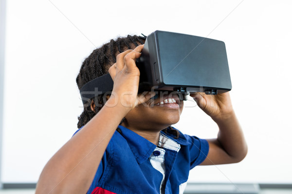 Stock photo: Smiling boy using virtual reality headset in classroom