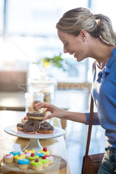 Excited woman selecting doughnuts from cake stand Stock photo © wavebreak_media