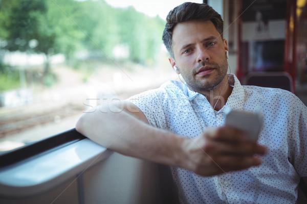 Jóképű férfi hallgat zene mobiltelefon vonat kutya Stock fotó © wavebreak_media