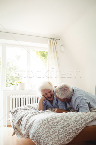 Senior couple interacting while relaxing on bed Stock photo © wavebreak_media