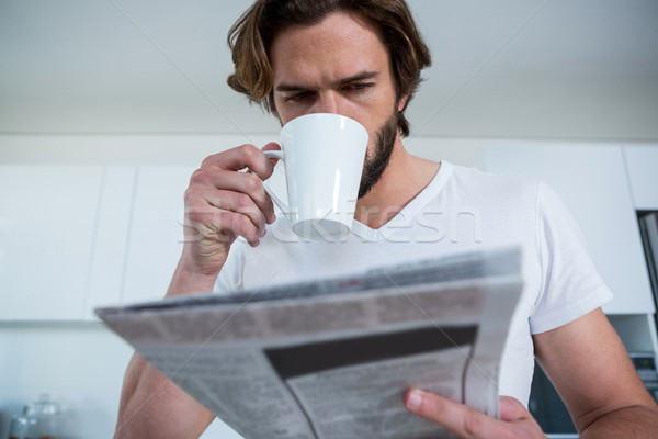 Stock photo: Man reading newspaper while having coffee in kitchen