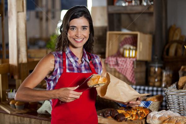 Mosolyog női személyzet csomagol édes étel papírzacskó Stock fotó © wavebreak_media