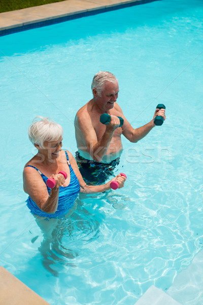 Senior couple exercising with dumbbells in the pool Stock photo © wavebreak_media