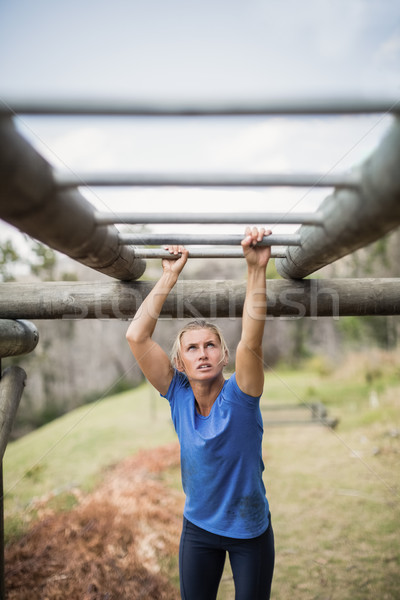Fit woman climbing monkey bars during obstacle course Stock photo © wavebreak_media