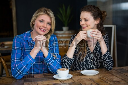 Portrait of smiling woman with coffee cups on table in cafe Stock photo © wavebreak_media