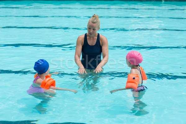 Female instructor assisting children in swimming pool Stock photo © wavebreak_media