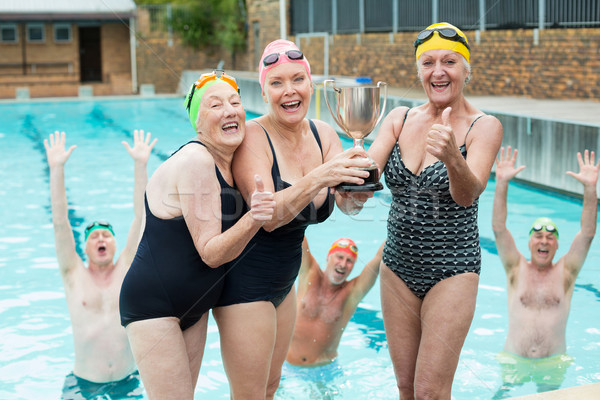 Senior female swimmers holding trophy at poolside Stock photo © wavebreak_media