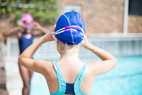 Girls adjusting swimming goggles at poolside Stock photo © wavebreak_media