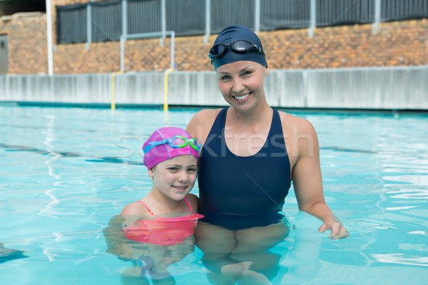 Portrait of female instructor and young girl standing in pool Stock photo © wavebreak_media