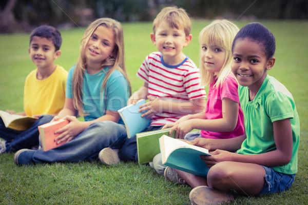 Mosolyog osztálytársak ül fű tart könyvek Stock fotó © wavebreak_media