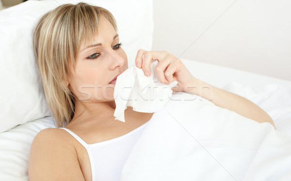 Upset sick woman blowing lying on her bed  Stock photo © wavebreak_media