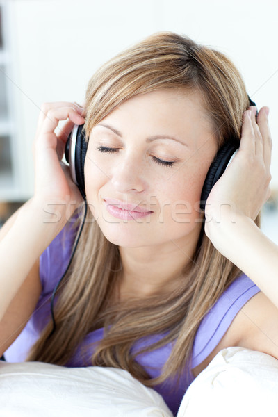 Portrait of a cheerful woman listening music in the kitchen  Stock photo © wavebreak_media